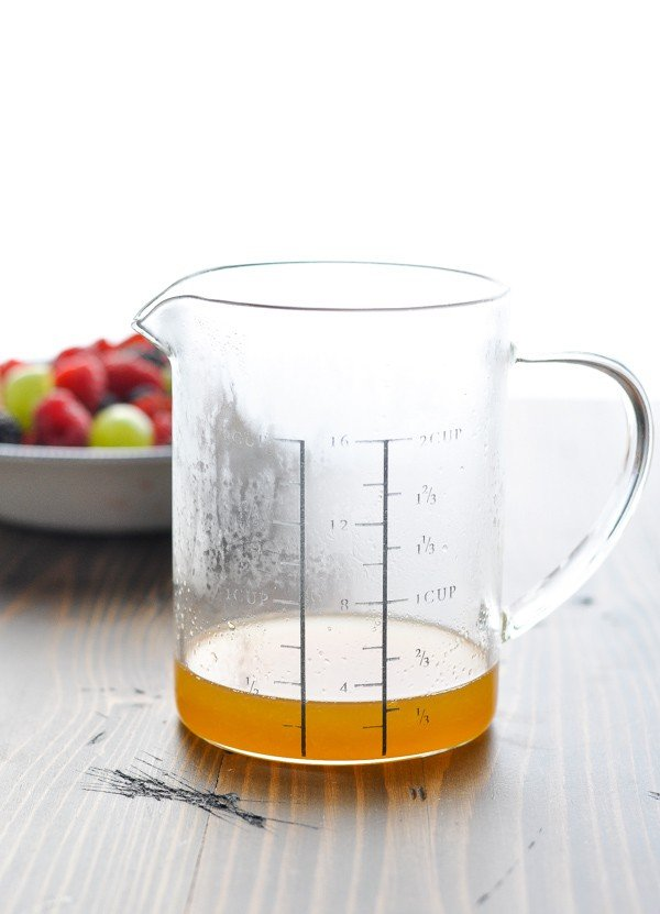 Honey lemon fruit salad dressing in a glass measuring cup