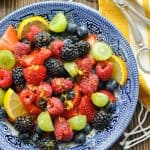 Close overhead shot of half a bowl of fresh fruit salad recipe with honey lemon dressing