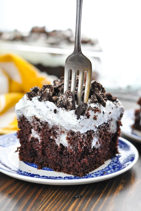 Fork slicing into a piece of Oreo Pudding Poke Cake