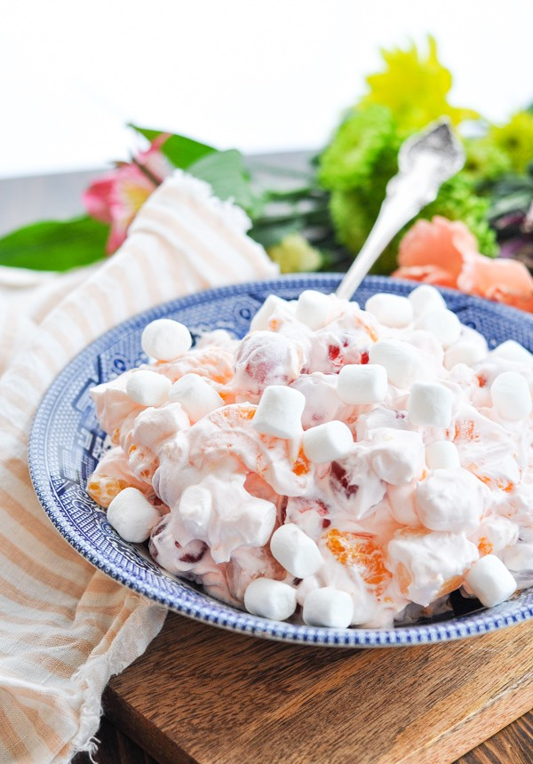 Close up front shot of a big bowl of Pink Ambrosia Salad with a serving spoon in the bowl