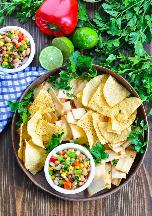 Overhead image of a tray of Texas Caviar with tortilla chips and pita chips
