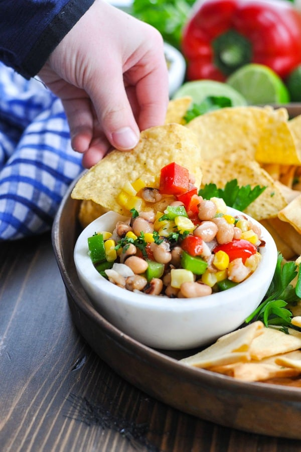 Tortilla chip scooping up Texas Caviar from a white bowl