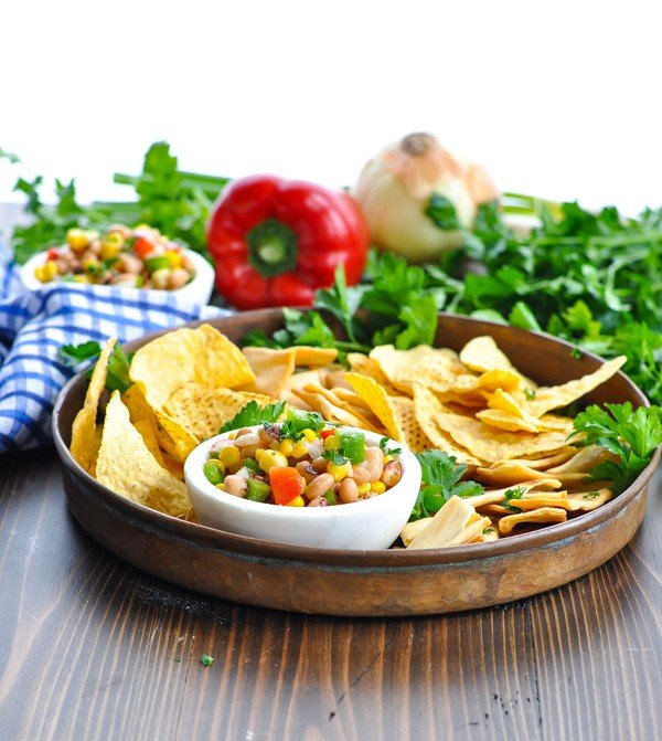 A copper appetizer tray full of chips and Texas Caviar dip