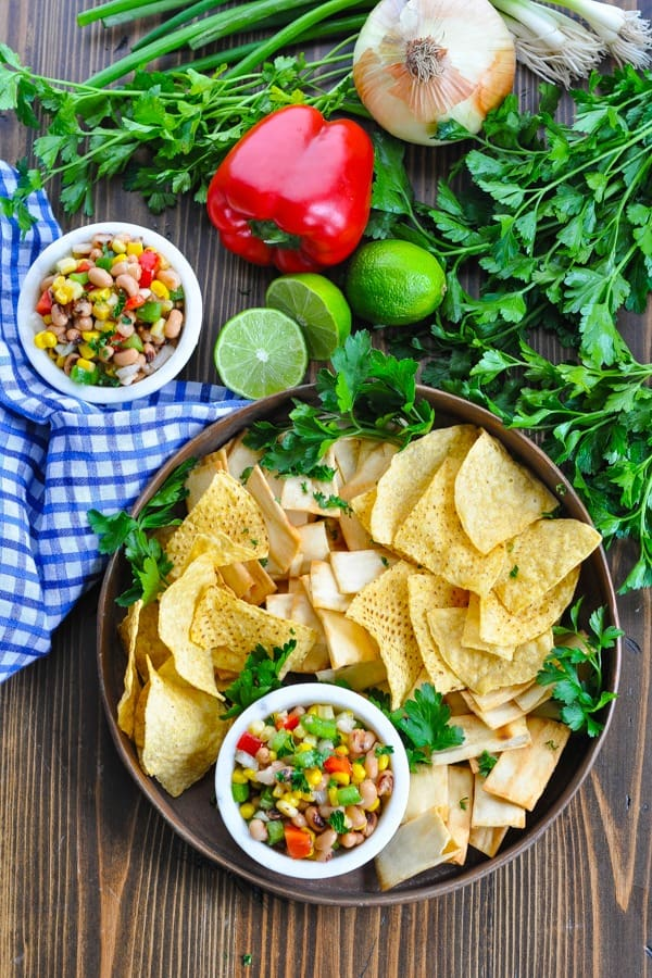 Overhead shot of Texas Caviar dip surrounded by tortilla chips and fresh vegetables