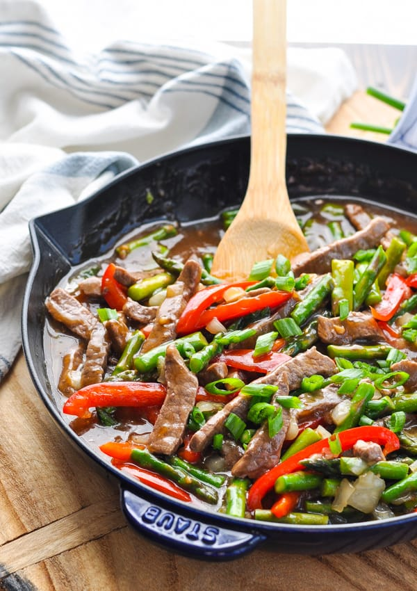 Front shot of wooden spoon in a skillet with beef and vegetable stir fry