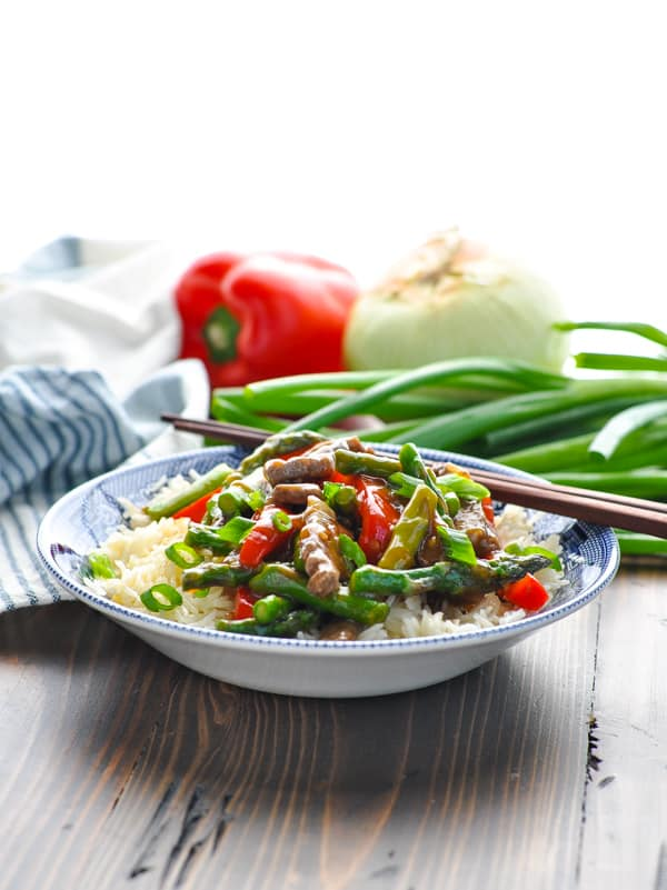 Vegetables and beef stir fry in blue and white bowl with chop sticks
