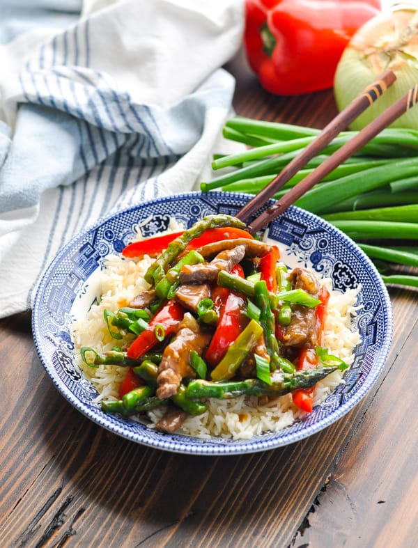 Asparagus and beef stir fry served over bowl of rice