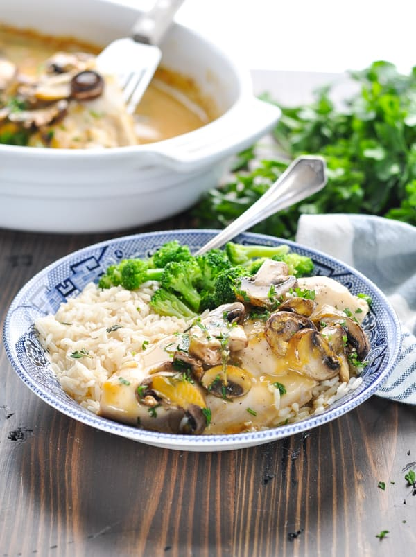 Chicken marsala served in a blue and white bowl and garnished with fresh parsley