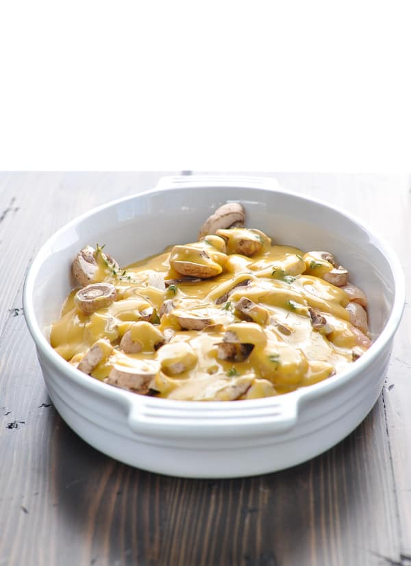 Raw chicken marsala in a white casserole ready to go in the oven