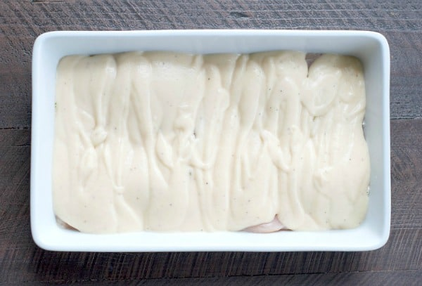 Alfredo sauce covering raw chicken breast in white dish