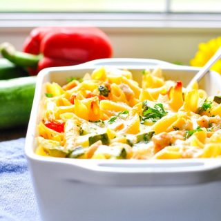 Summer pasta with zucchini, tomatoes and corn in a white casserole dish in front of a window