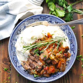 Bowl of braised steak and vegetables over mashed potatoes
