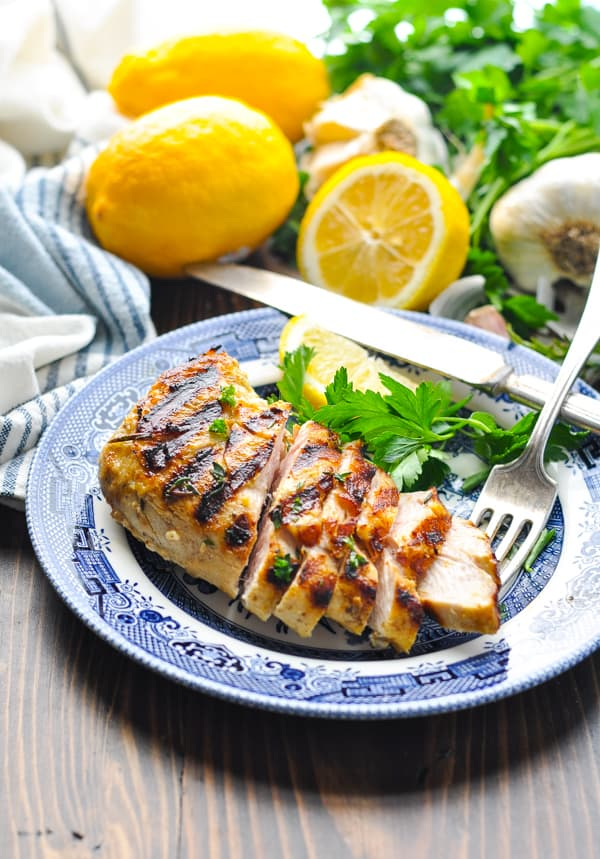 Sliced grilled chicken on a plate with fresh parsley