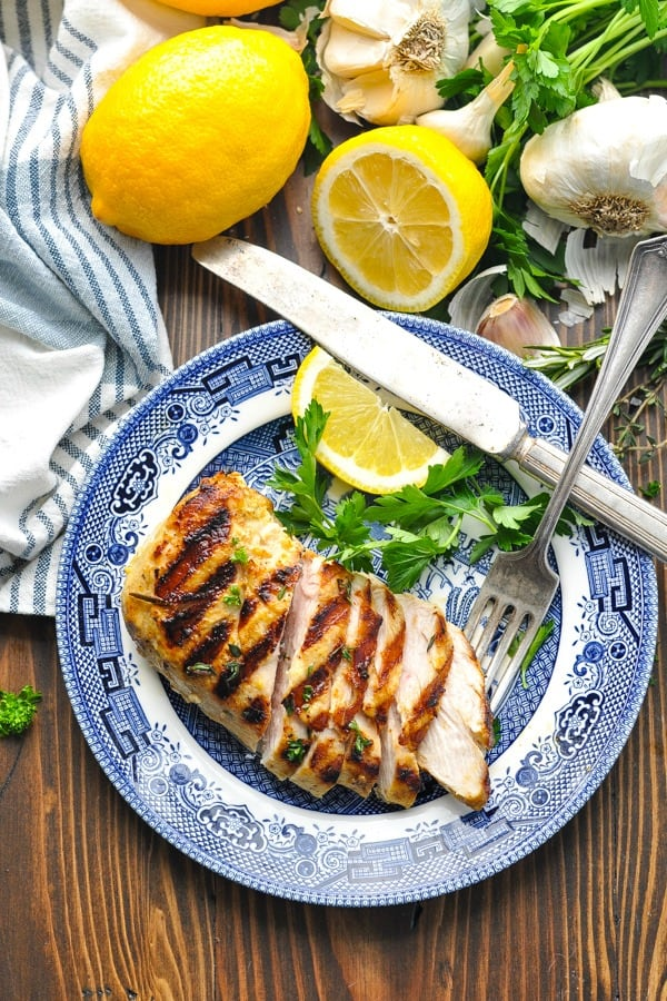 Overhead shot of grilled chicken on a plate with a fork and knife