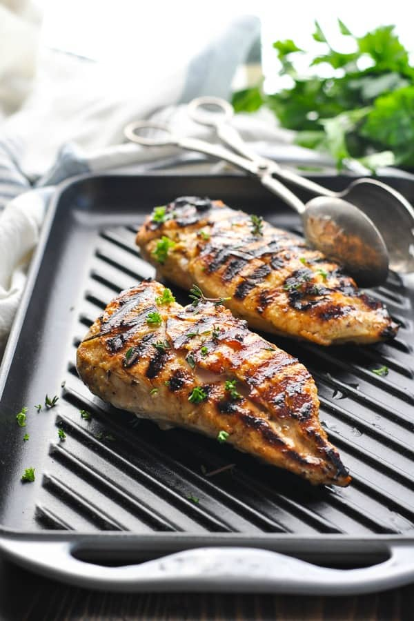 Two grilled chicken breasts on an indoor grill pan