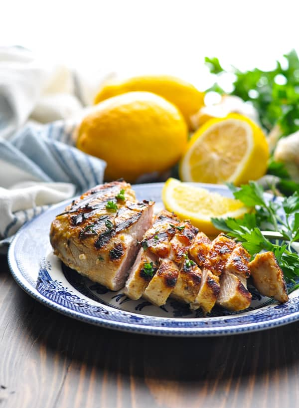 Marinated grilled chicken on a plate with lemon and herbs