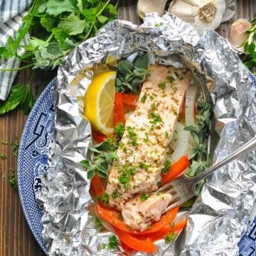 Overhead shot of foil pack salmon on a plate with a fork
