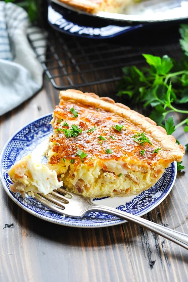 Quiche Lorraine on a plate with a bite on a fork and fresh parsley garnish