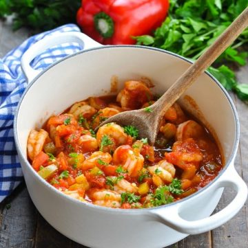 Easy shrimp creole recipe in a white Dutch oven with a wooden serving spoon
