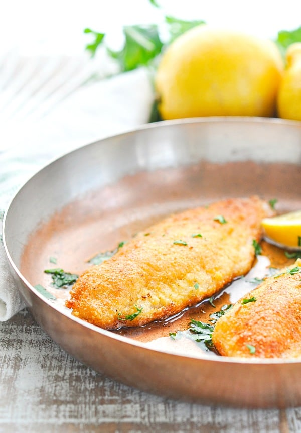 Close up shot of fried catfish in a copper skillet with lemons in the background