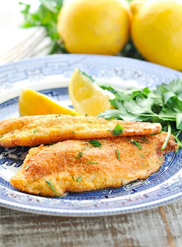 Fried catfish on a blue and white plate with lemon wedges