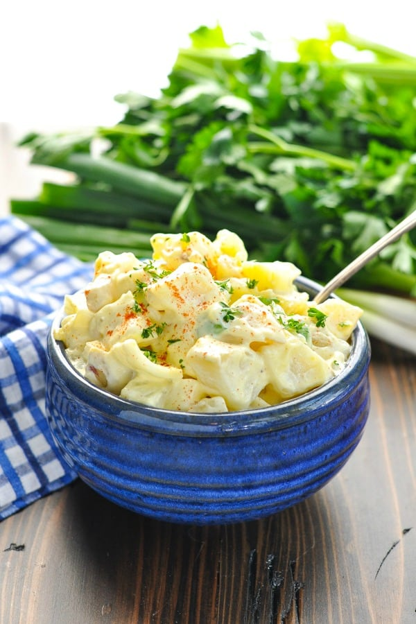 Creamy potato salad in a blue bowl with silver serving spoon