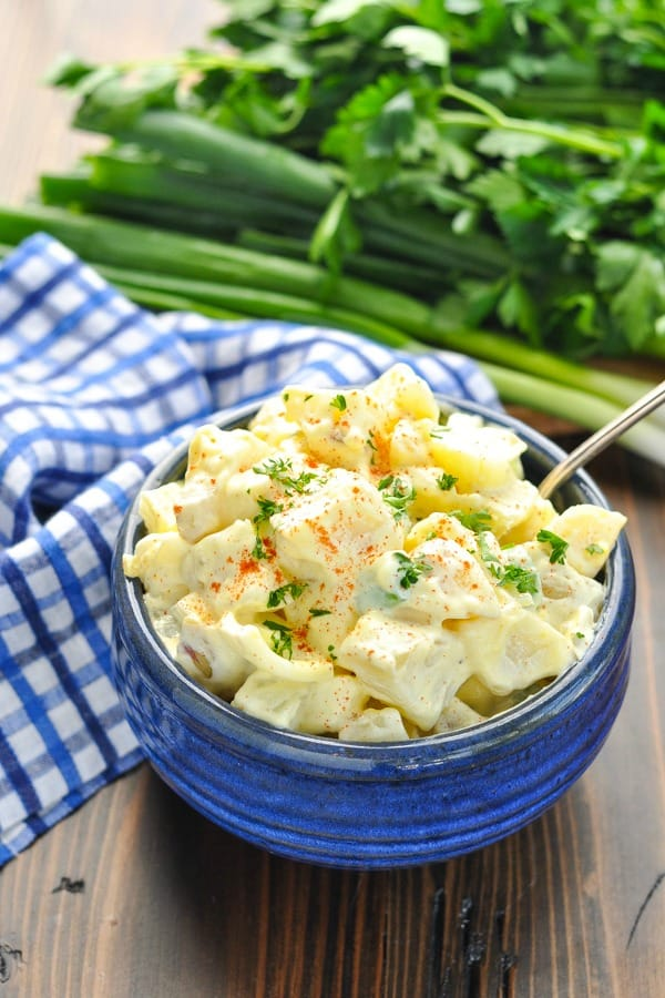 Bowl of potato salad with parsley and green onions in the background