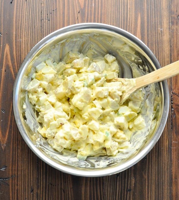 Overhead shot of southern potato salad in large mixing bowl with wooden spoon