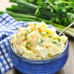 Bowl of potato salad garnished with parsley and paprika
