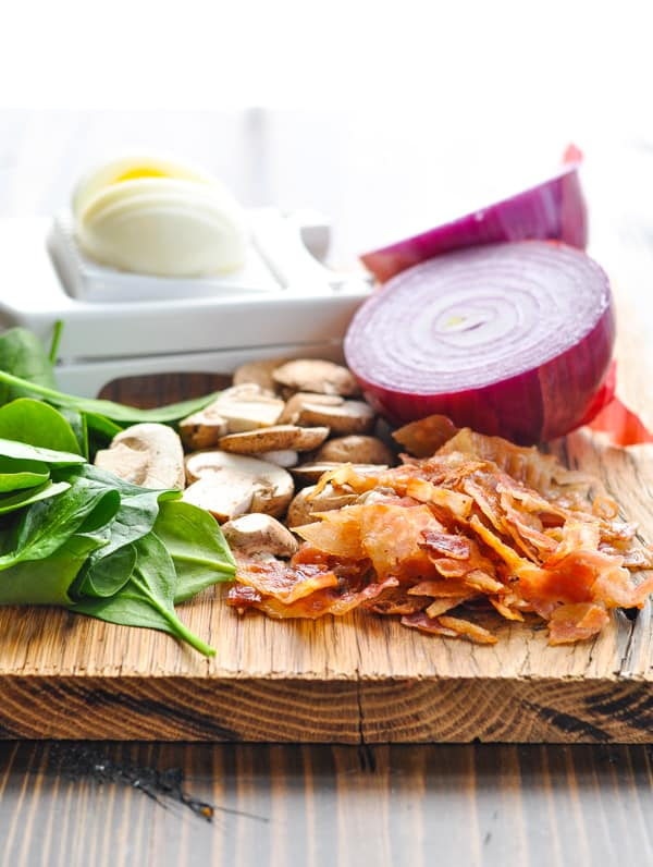 Spinach and bacon salad ingredients on a cutting board