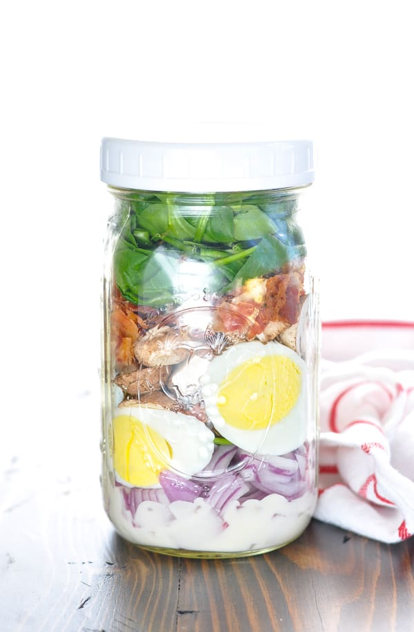 Spinach salad in a jar with a red and white towel in the background