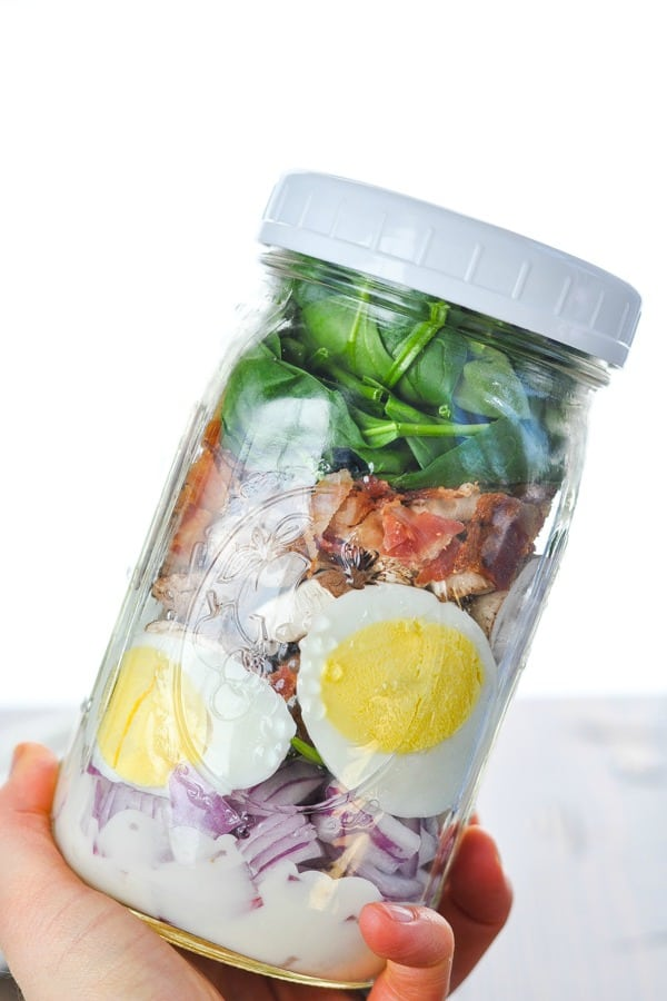 Hand holding a spinach salad in a jar
