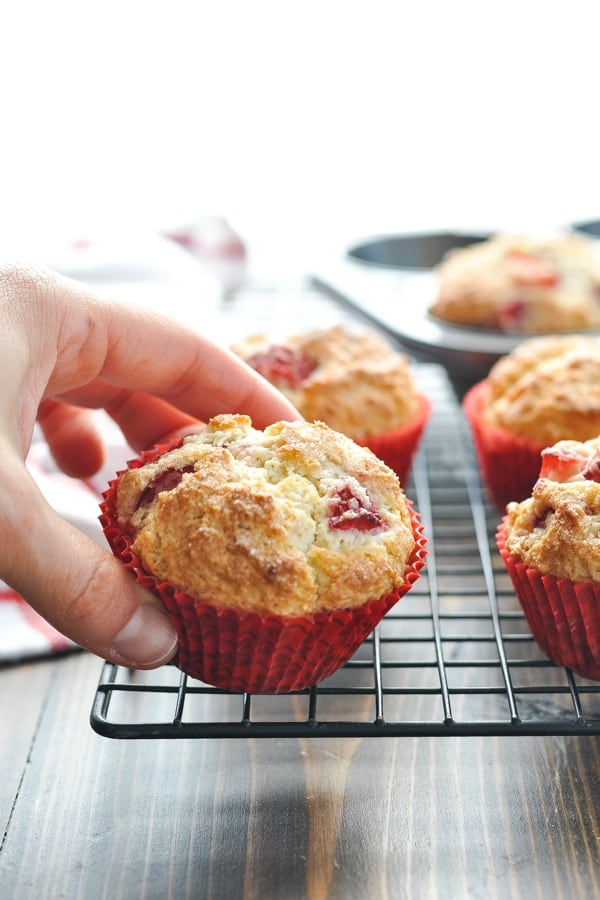 Hand picking up a strawberry muffin on the cooling rack