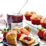 Strawberry Muffins on a blue and white plate with strawberry preserves in the background