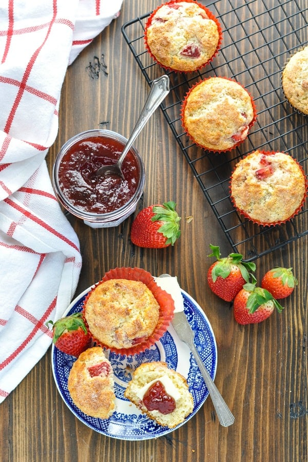 Long overhead shot of strawberry muffins on a table with fresh berries and strawberry jam