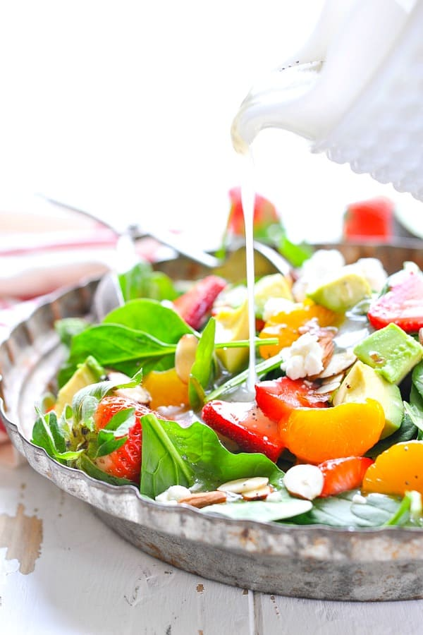 Pouring poppy seed dressing over a spinach salad with strawberries nuts and cheese