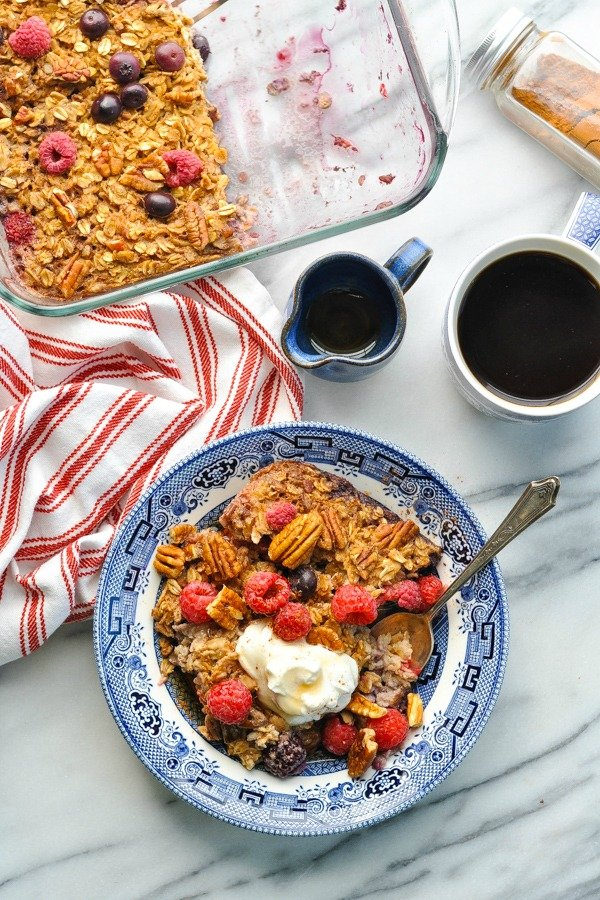 Overhead shot of baked oatmeal on a plate with coffee and the casserole dish nearby
