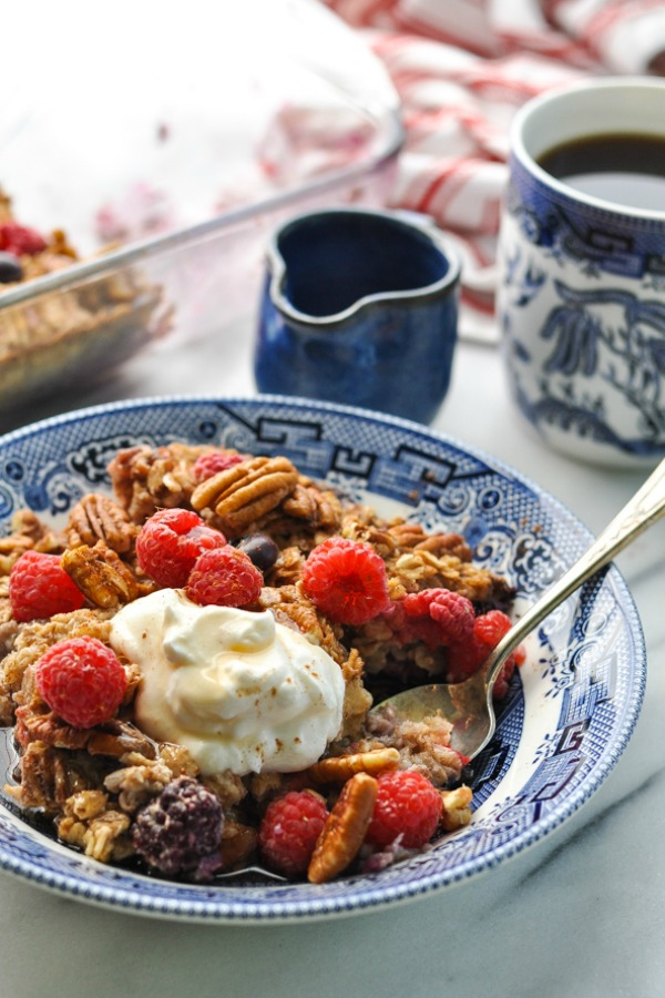 Close up shot of berry oatmeal bake in a blue and white bowl with yogurt on top