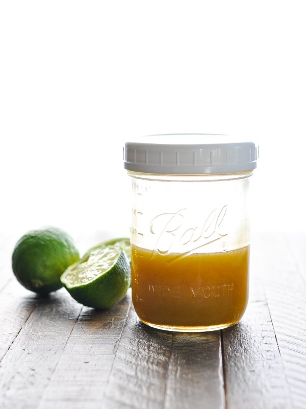 Dressing for Black Bean and Corn Salad in a mason jar with fresh limes