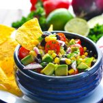 Blue bowl full of Black Bean and Corn Salad with tortilla chip for dipping