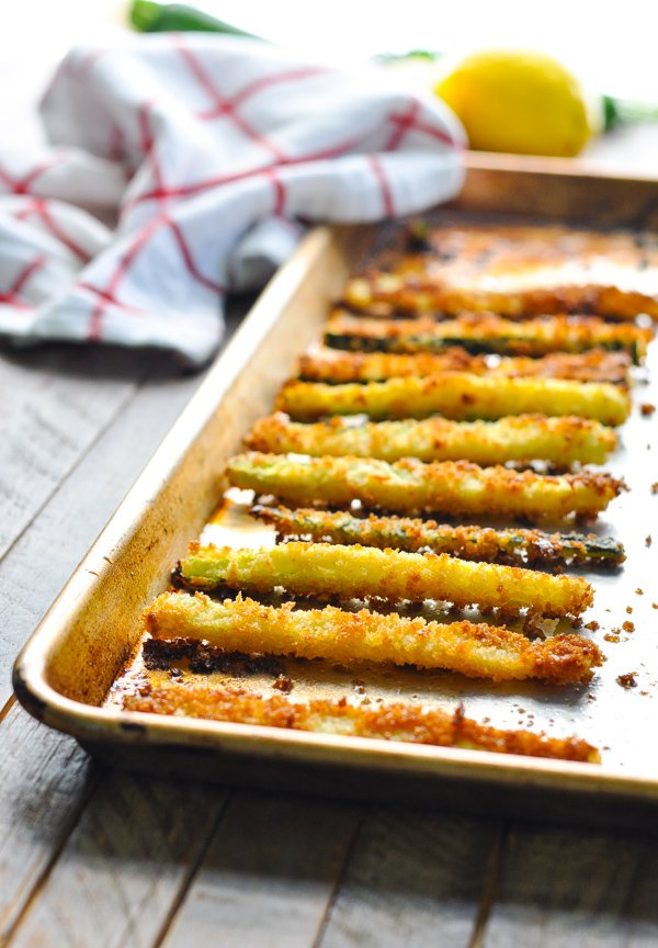 Crispy golden brown zucchini fries on a baking sheet