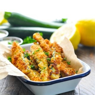 Bright shot of crispy zucchini fries in a blue and white dish with lemons in the background