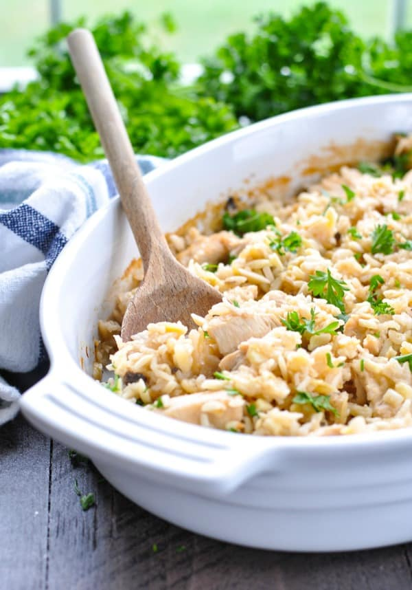 Chicken and rice pilaf in a dish with a wooden serving spoon