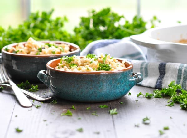 Horizontal shot of two bowls of rice pilaf and chicken breast on a table