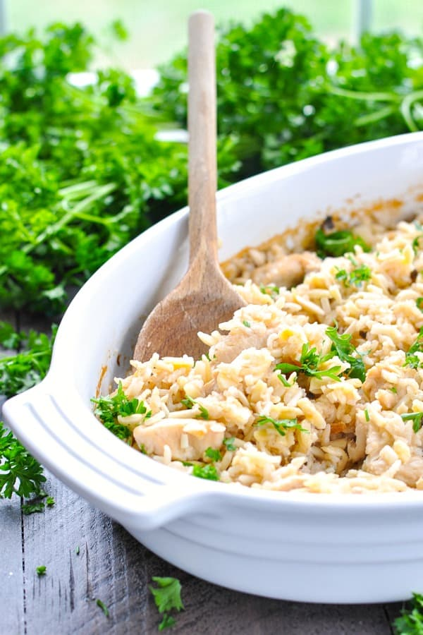 Chicken and rice pilaf casserole in a white baking dish with wooden spoon
