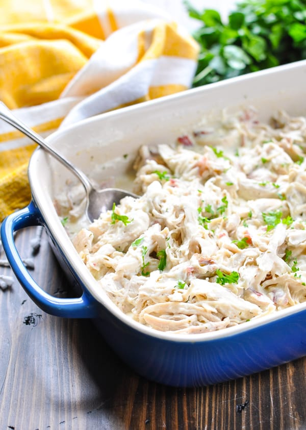 Shredded cream cheese Ranch chicken in a baking dish with a silver serving spoon