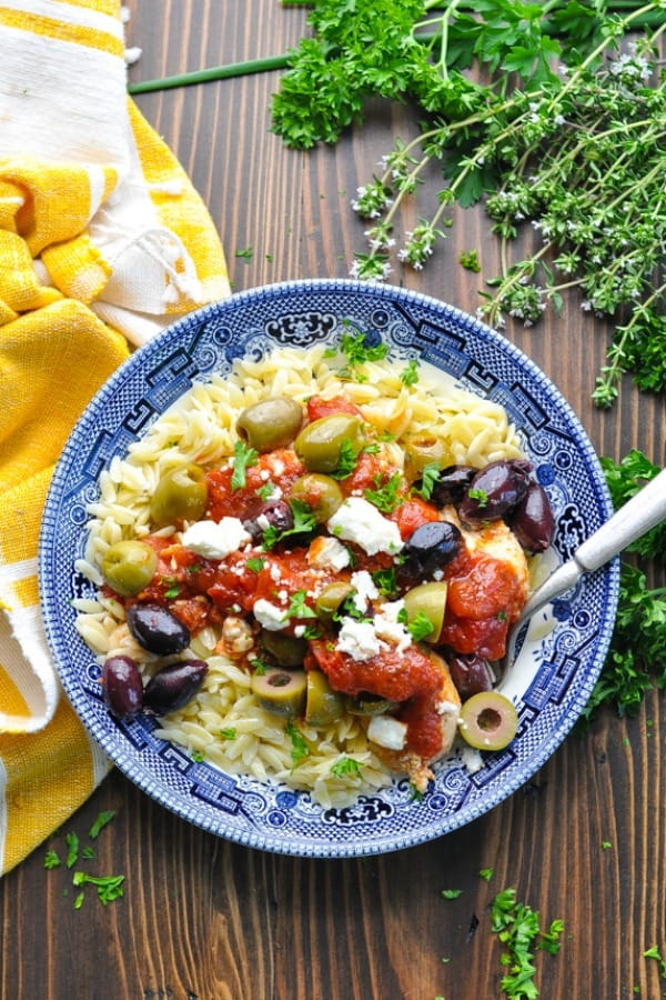 Overhead shot of mediterranean chicken in a bowl of pasta with herbs surrounding the bowl