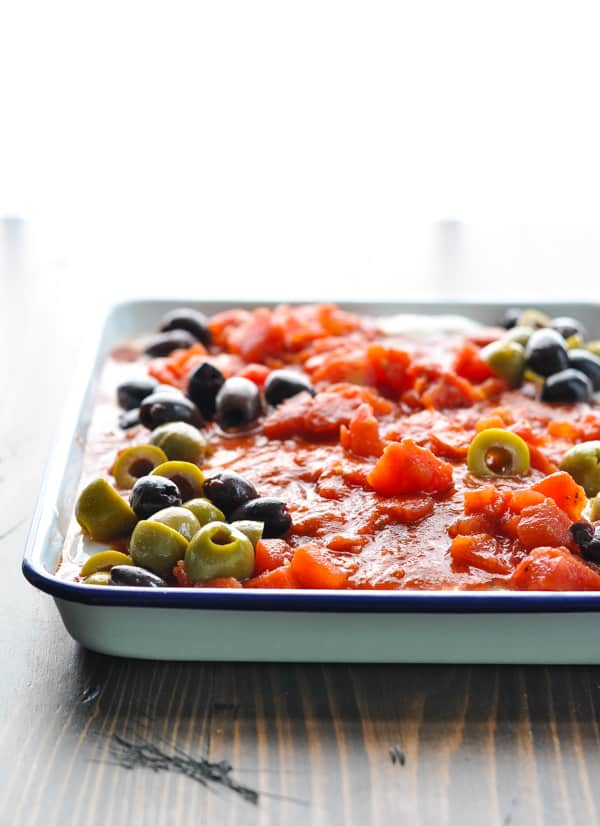 Olives added to mediterranean chicken dish before it goes in the oven