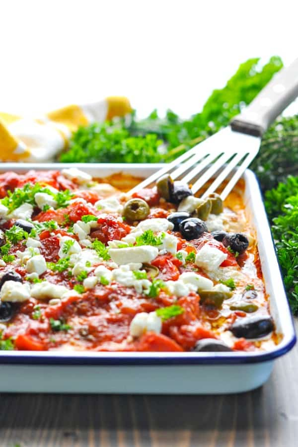 Front shot of mediterranean chicken baked in a blue and white pan garnished with fresh parsley and feta cheese