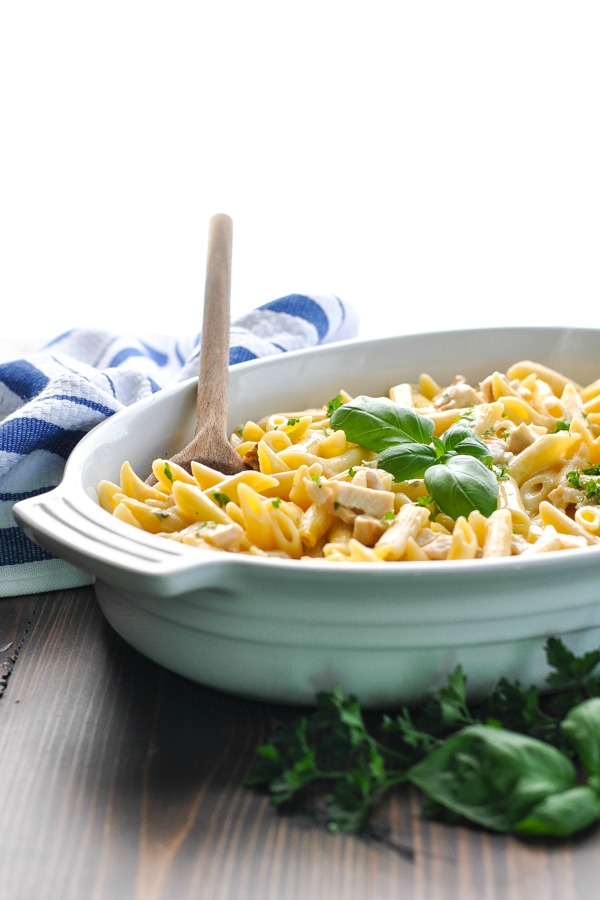 Parmesan Penne Pasta in a white casserole dish with a wooden serving spoon